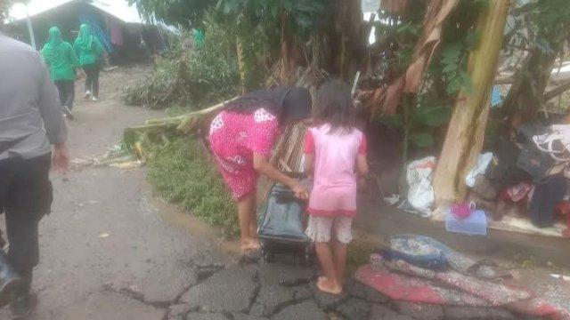 Warga korban Jeneponto membersihkan sisa-sisa banjir menggunakan air bercampur lumpur.